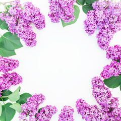 Floral frame of purple lilac branches and leaves on white background. Flat lay, top view. Summer pattern