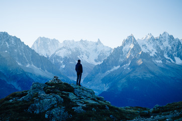 Man looking at the mountains near Chamonix, France. Old film style. Wall mural