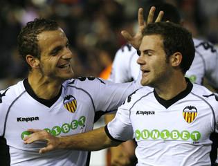 Valencia's Soldado congratulates team mate Mata after he scored against Bursaspor during their Champions League Group C soccer match in Valencia