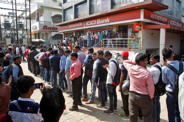 People queue outside a bank to exchange and deposit their old high denomination banknotes in Allahabad