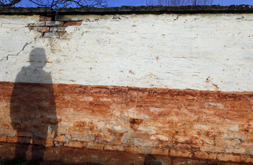 The shadow of a man is cast on the wall marked by caustic red mud in Devecser