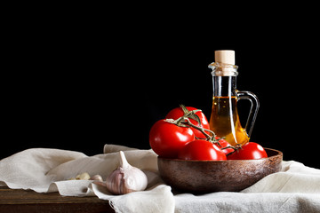 Still life of tomatoes, garlic and olive oil on wooden boards. On a black background.