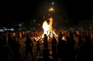 Hindu devotees walk around a bonfire during a ritual known as Holika Dahan which is part of Holi celebrations in Ahmedabad