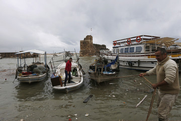 Fishermen attempt to anchor their boats amidst a storm and strong winds at the harbour of the ancient city of Byblos, in northern Beirut