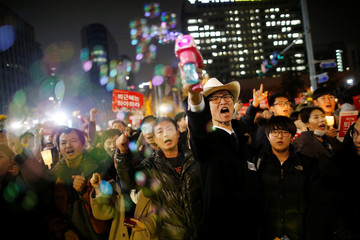 A man uses a bubble gun as he and others chant slogans on a road leading to the Presidential Blue House during a protest calling South Korean President Park Geun-hye to step down, in Seoul