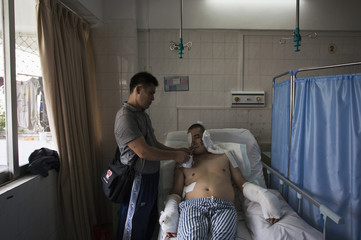 Li Jianhuang feeds his brother, blogger and online whistleblower Li Jianxin, who is waiting for a fourth operation at a hospital in the southern Chinese city of Huizhou