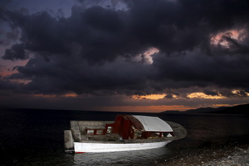 A boat used by refugees and migrants to travel across the Aegean Sea from the Turkish coast in the Greek island of Lesbos is seen at a beach