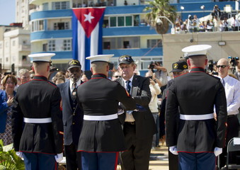 Retired marines present the U.S. flag to Marines currently stationed in Cuba, during the raising of the U.S. flag over the newly reopened embassy in Havana