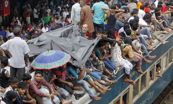 People shelter under a sheet of plastic as they crowd on top of a train as it enters the Dhaka airport rail station as thousands of Bangladeshi Muslims head home to celebrate Eid-al-Adha.
