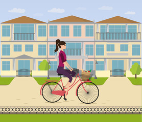 A girl rides a bicycle home in her neighborhood. Woman is cycling from shop with  bag with food