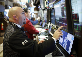 Traders handle last minute trade orders on the floor of the New York Stock Exchange just before the closing bell