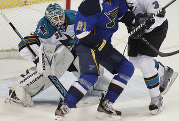 San Jose Sharks' goalie Niemi works to keep his eyes on the puck as defenseman Murray works to clear St. Louis Blues' Berglund from the front of the net in the 2nd period of their NHL Western Conference quarterfinal playoff hockey game in St. Louis