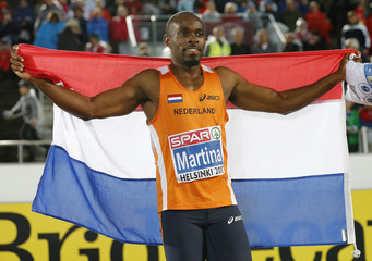 Martina of the Netherlands poses with his national flag after winning the men's 200 metres final at the European Athletics Championships in Helsinki