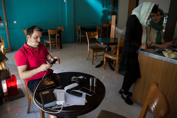 Man uses his smartphone to follow election news in a coffee shop in Tehran