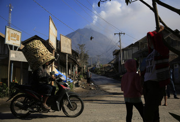 A villager wears a basket as he heads to the market as Mount Sinabung spews ash at Payung village in Karo district