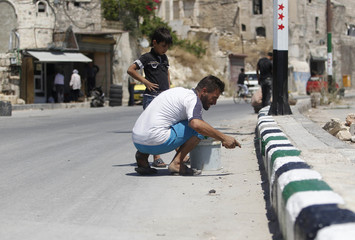 A man paints a sidewalk with the colours of the Syrian opposition flag in the old city of Aleppo