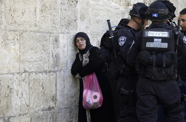 A Palestinian woman waits as Israeli policemen prevent people from entering the compound which houses al-Aqsa mosque in Jerusalem's Old City