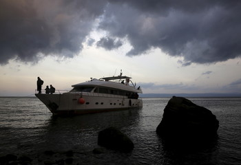 Syrian refugees wait to disembark from a luxury yacht used by about 250 Syrian refugees to travel across the Aegean Sea from the Turkish coast in the Greek island of Lesbos