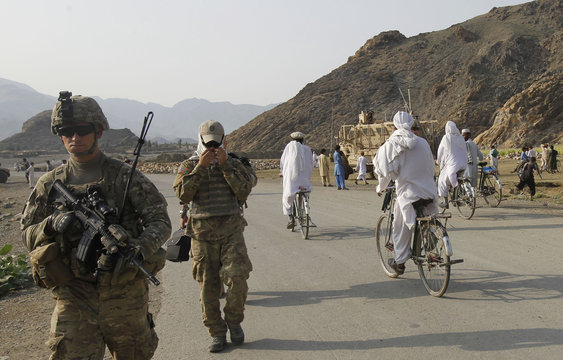 """A U.S. soldier from 127th Military Police Task Force """"Cacti"""" and a linguist walk along a road during a patrol in Khas Konar district in Kunar"""