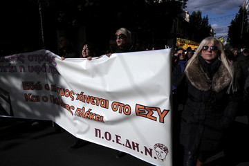 Health workers shout slogans during a demonstration against government plans affecting their sector, in Athens