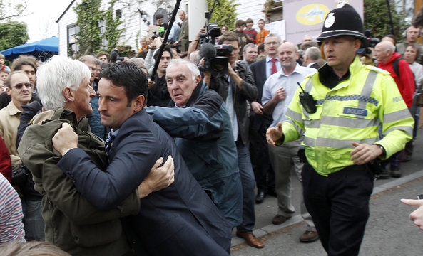 A man is restrained by police officers as a scuffle broke out during the visit of Liberal Democrat leader Nick Clegg to Malvern, Worcestershire