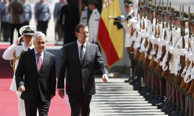 Chile's President Pinera and Spain's PM Rajoy walk past a honor guard at the La Moneda Presidential Palace in Santiago