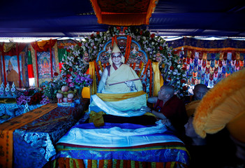 A Tibetan monk arranges a cardboard portrait of Dalai Lama during his birthday celebration in Kathmandu