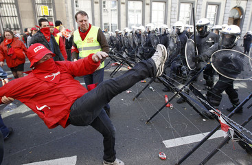A demonstrator taunts riot police during a protest in Brussels