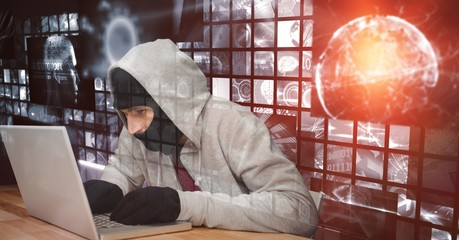 Digital composite image of hacker using laptop