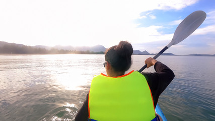 Back View of asian woman kayaking at the beach with life jacket