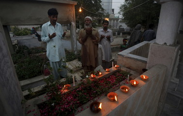 Men pray over the grave of their family member while observing the Shab-e-Barat festival at a cemetery in Karach