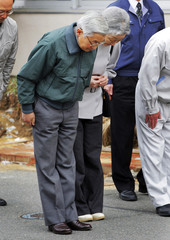 Japan's Emperor Akihito and Empress Michiko pay tribute to victims of the deadly earthquake and tsunami last month as they visit a damaged fishing port in Otsu town