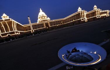 "The Indian Home Ministry is illuminated as it is reflected on a brass band instrument during the rehearsal for the ""Beating the Retreat"" ceremony in New Delhi"