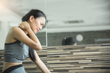 Asian woman having neck pain after workout.