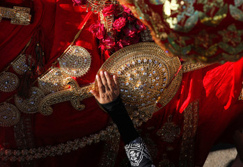 A hand of a Shi'ite Muslim woman touches the gold-ornamentation of sword and shield, placed on a symbolic sacred horse for a good luck, during Chelum, a procession to mark the fortieth day after the death of Imam Hussain, grandson of the Prophet Muhammad,