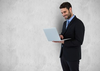 Businessman using laptop against gray background