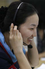 A foreign currency dealer of the Korea Exchange Bank smiles as she talks on a phone at the bank's dealing room in Seoul