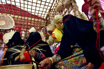 A woman arranges yarn to be used in the design of handmade date baskets during the Liwa Date Festival, in Liwa