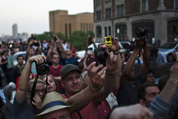 "People take pictures of sunset on 42nd street during the biannual ""Manhattanhenge"" in New York City"