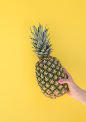 Girl's hand with pink nails holding a pineapple on yellow background
