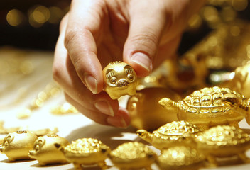An employee of a jewellery shop holds a gold pig during a photo opportunity at a jewellery shop at the Shinsegae department store in Seoul