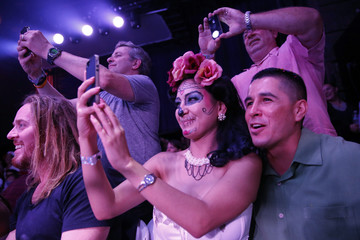"Audience members take pictures during the Lucha VaVoom ""Night of the Vampire"" performance in Los Angeles"