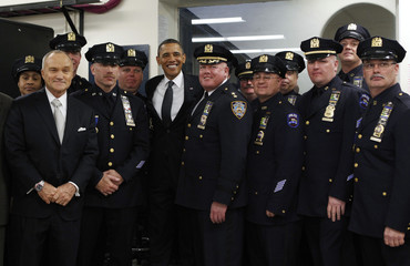 U.S. President Obama poses for a photo with officers and former Police Commissioner Kelly while visiting the First Precinct police station in New York