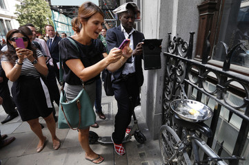 Pedestrians take photographs of an egg frying in a pan using heat from the reflected sunlight off the Walkie Talkie tower in London