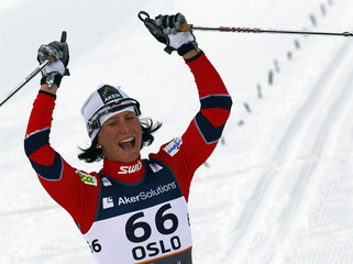 Bjoergen of Norway celebrates victory in the women's cross country individual classic 10 km race at the Nordic Ski World Championships in Oslo