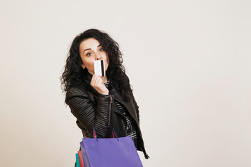 Fashionable young woman with credit card and colored shopping bags over white studio background.