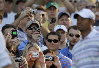 Fans and patrons take photos of Woods of the U.S. as he walks to the fourth tee as patrons crowd in to take his picture during a practice round for the 2010 Masters golf tournament at the Augusta National Golf Club in Augusta