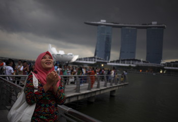 An Indonesian tourist poses for photos as storm clouds gather at the Merlion Park in Singapore