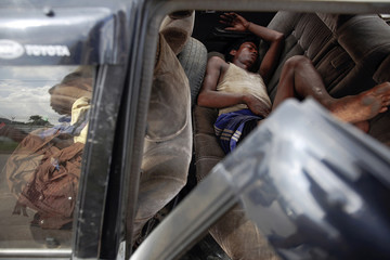 A man sleeps inside a car before taking it to a junkyard to exchange it for a new import license in Yangon's suburbs