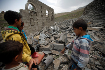 Children inspect damage at a house after it was destroyed by a Saudi-led air strike in Yemen's capital Sanaa